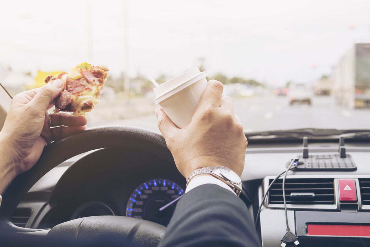 Man eating pizza and coffee while driving car dangerously