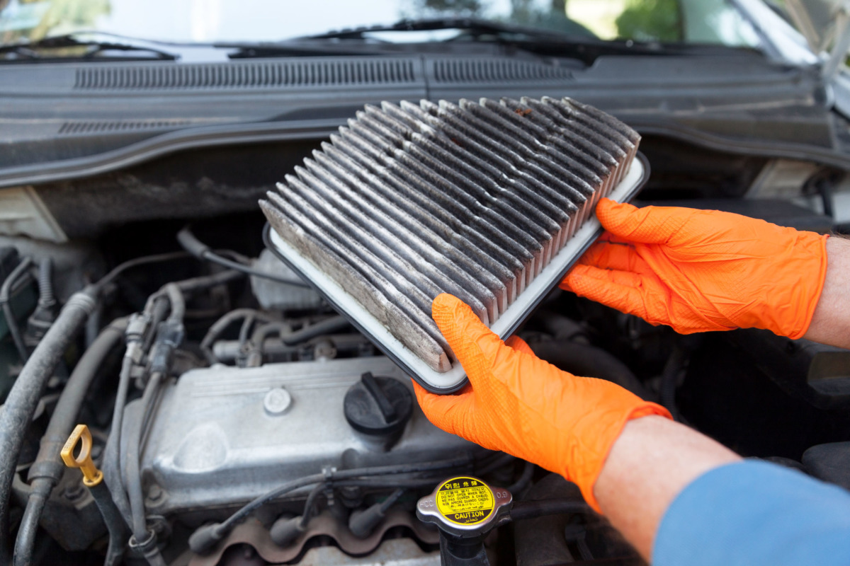 Auto mechanic wearing protective work gloves holding dirty air filter above a car engine