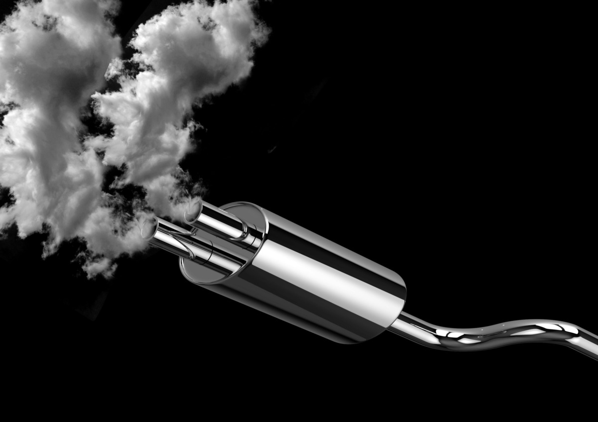 car pipe exhaust fumes and smoke isolated over black background. Concept of pollution of the environment caused by automobiles